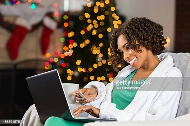 African American woman buying Christmas gifts online with credit card
