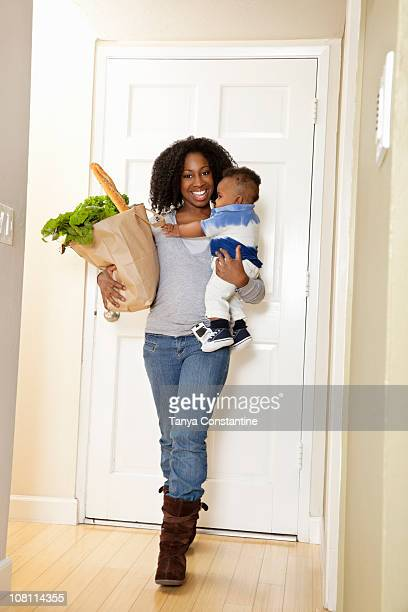 African American woman carrying bag of groceries and baby son