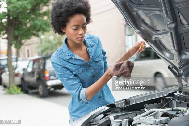 African American woman checking oil of car