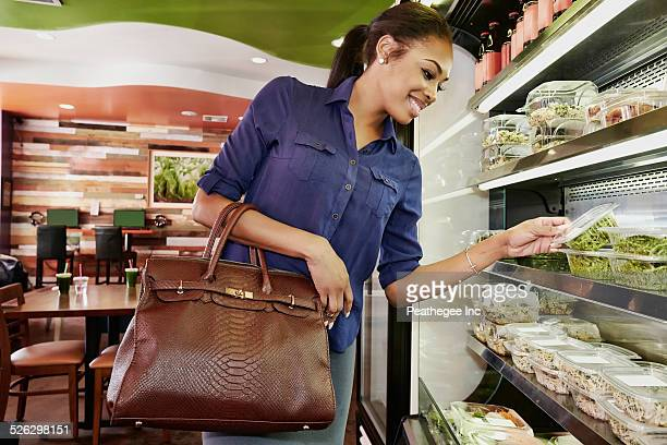 African American woman choosing food in deli