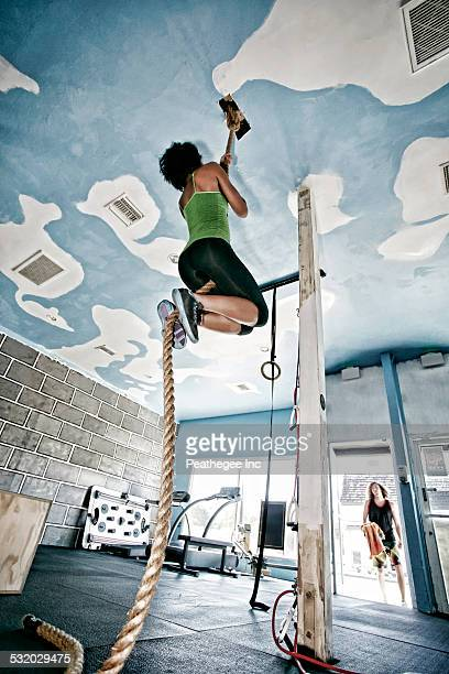 African American woman climbing rope in gym