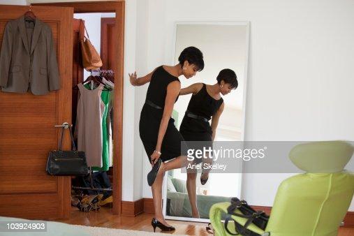 African American woman dressing in bedroom