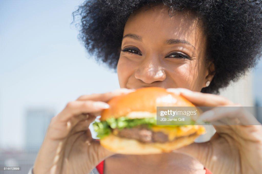 African American woman eating cheeseburger