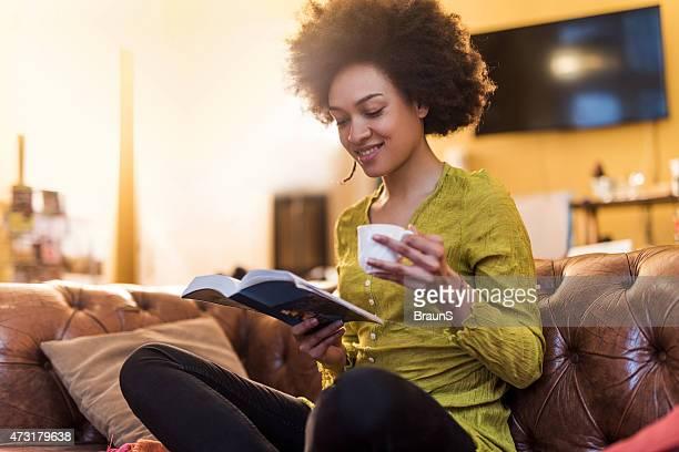 Afrikanische amerikanische Frau, die Lektüre eines Buches zu Hause fühlen.