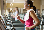 African American woman exercising on treadmill in gym