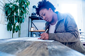 Millennial female black woman fills out a job application at a wood work table.