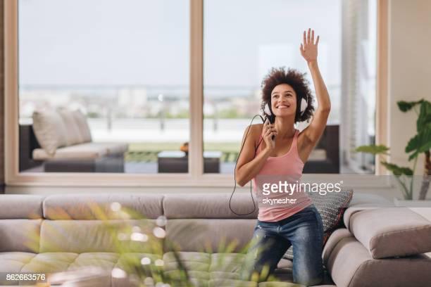 リビング ルームで携帯電話で音楽を聴いて楽しくアフリカ系アメリカ人の女性。
