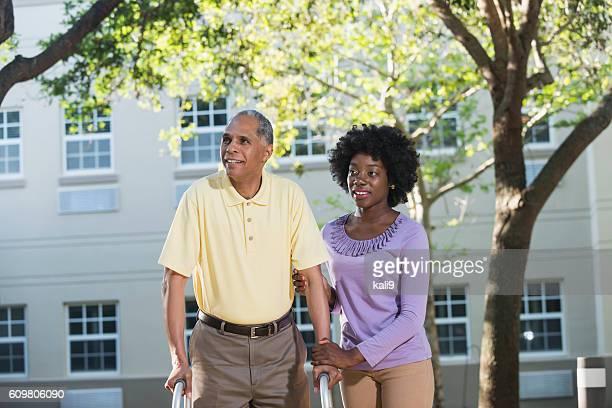 Afroamerikanische Frau helfen Ihrem Vater mit walker