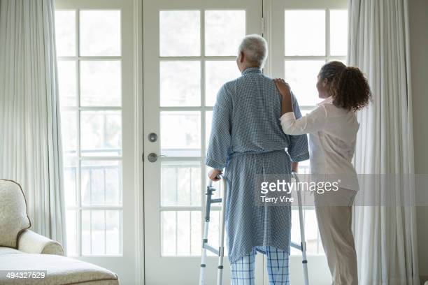African American woman helping Senior man use walker