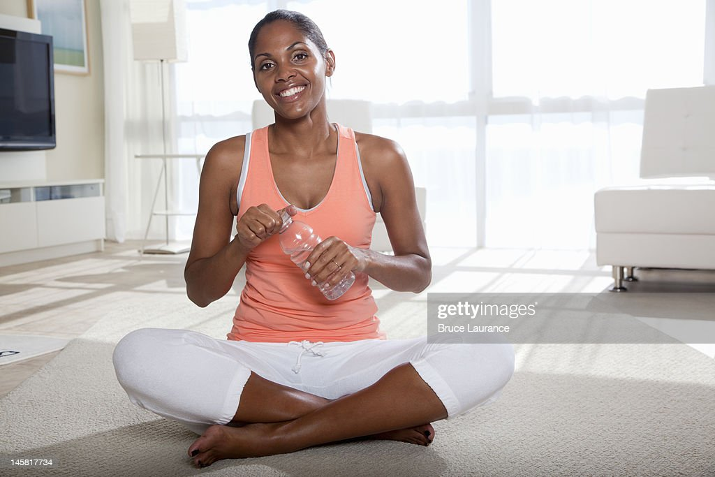 African American woman holding bottle of water : Stock Photo