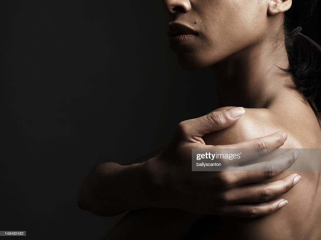 African American woman holding her shoulder : Stock Photo