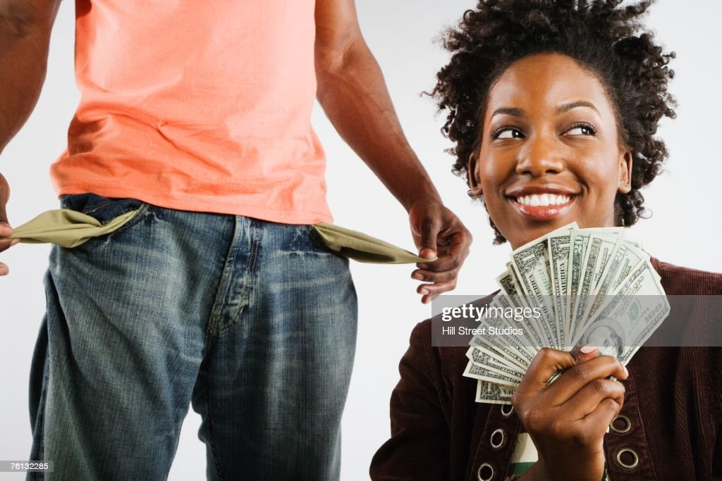 African American woman holding money next to man with empty pockets : Stock Photo