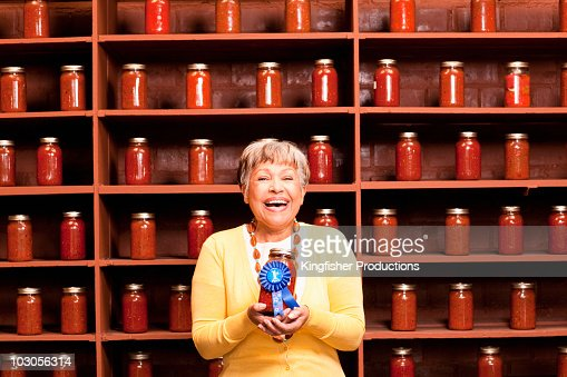African American woman holding prize-winning jar of sauce