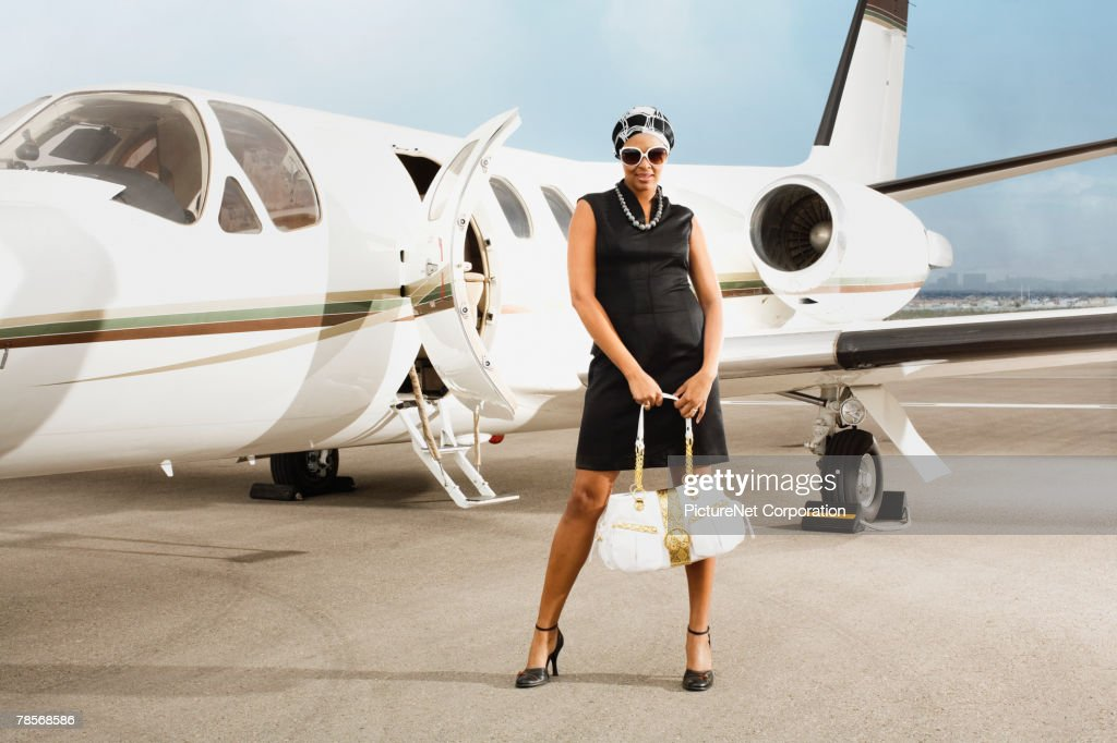 African American woman in front of airplane