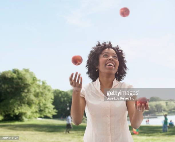 African American woman juggling fruit in park