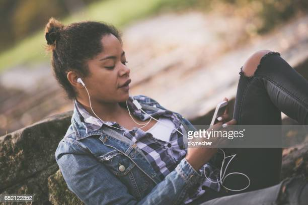 African American woman listening music over mobile phone in nature.