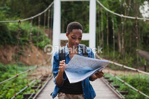 African American woman looking at a map travel and explore concept : Stock Photo