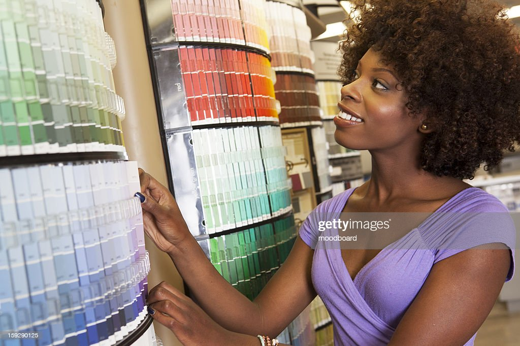 African American woman looking at paint swatches at hardware store : Stock Photo