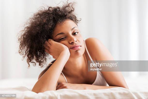 African American woman lying in bed and looking at camera.