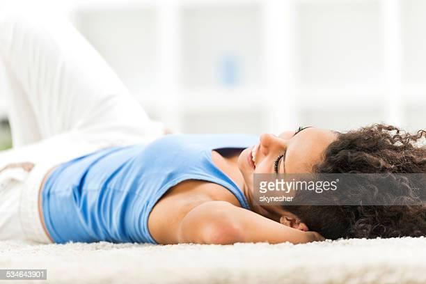 African American femme allongée sur le tapis.