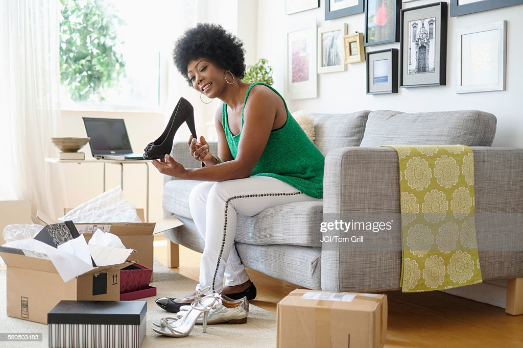 African American woman opening packages of shoes on sofa : Stock Photo