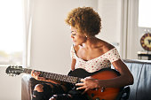 african american woman playing guitar at home sitting on futon