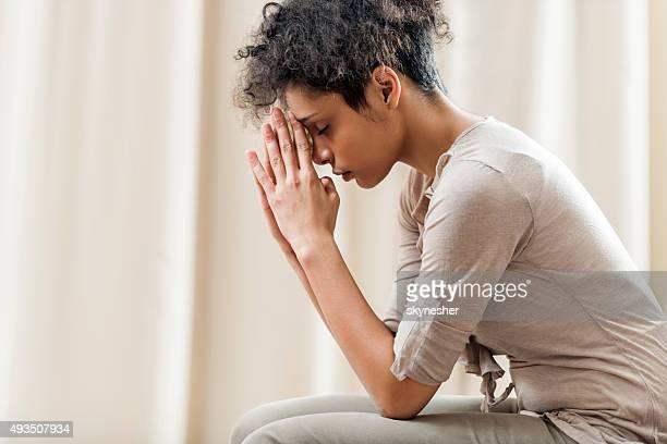 praying femme afro-américaine à la maison.