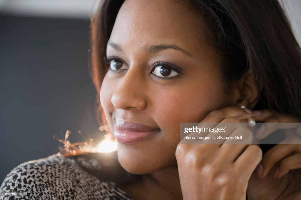 African American woman putting on earrings : Stock Photo