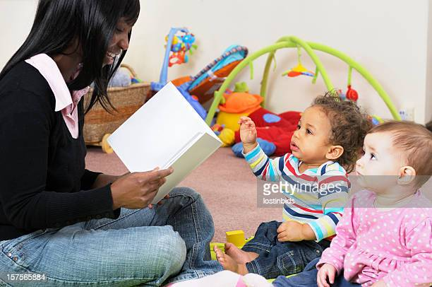 African American Woman Reading A Story To Group of Babies