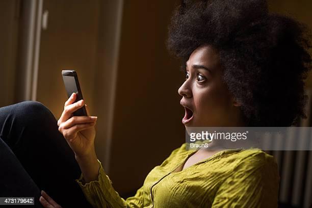Afrikanische amerikanische Frau, die eine SMS-Nachricht schockierend.
