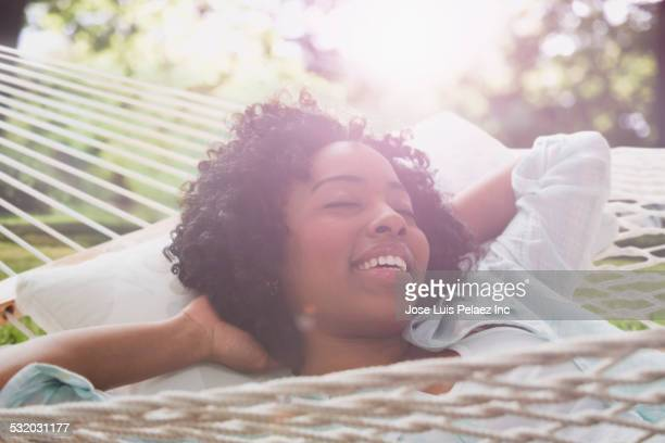 African American woman relaxing in hammock