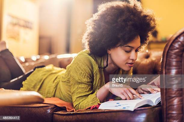African American woman relaxing on sofa and reading a book.