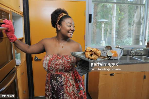 African American woman removing checking from oven
