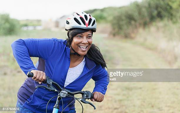 African American woman riding bike in park