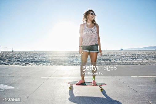 African American woman riding longboard on beach