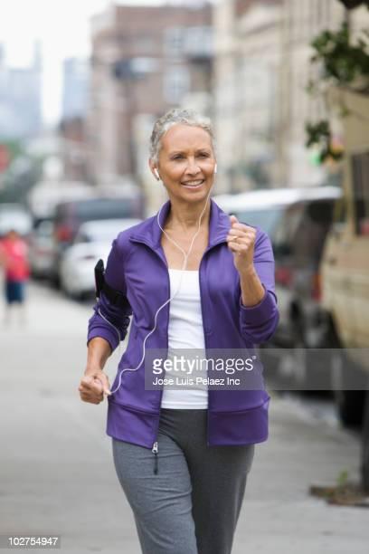 African American woman running on city sidewalk