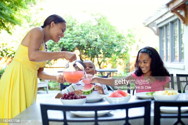 African American woman serving juice to daughter
