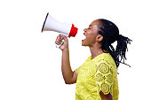 Profile view of African American woman shouting at megaphone while standing against white background