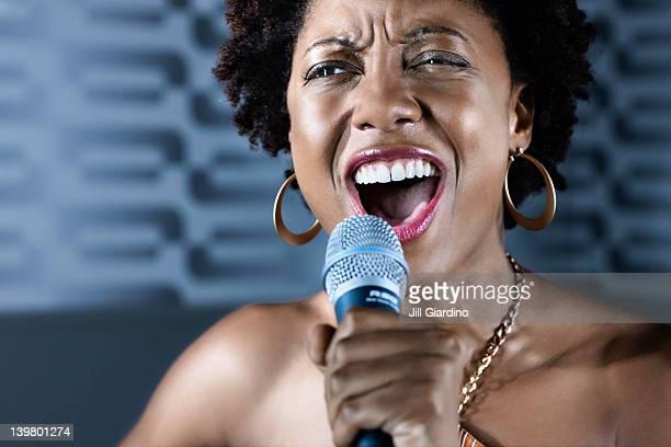 Afrikanische amerikanische Frau singen karaoke im nightclub