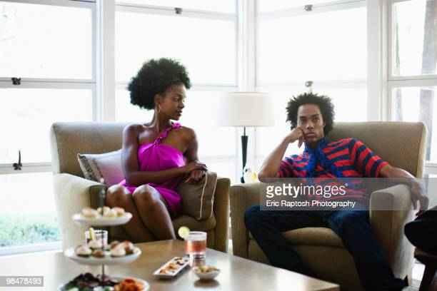 African American woman sitting at cocktail party with boyfriend