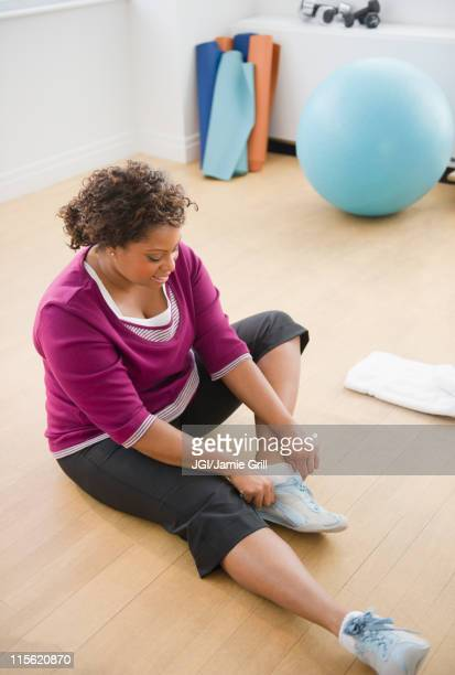 African American woman sitting on floor putting on shoes