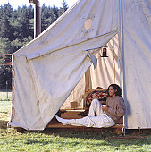 African American Woman Sitting Outside Her Tent On A Mountain Morning