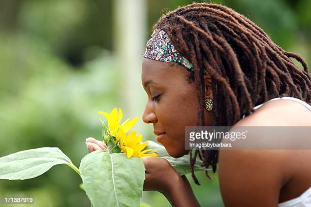 African American Woman Smelling a Sunflower.
