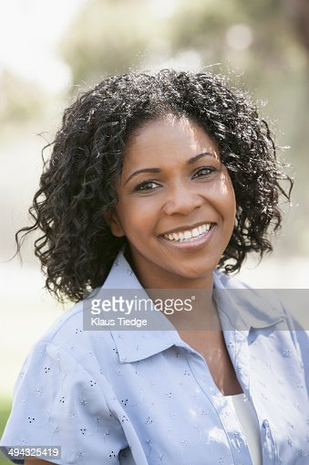 African American woman smiling outdoors : Stock Photo