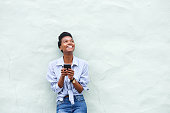 Portrait of african american woman smiling with mobile phone and looking up