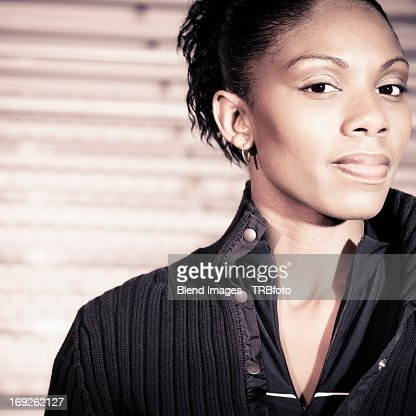 African American woman standing by bleachers : Stock Photo