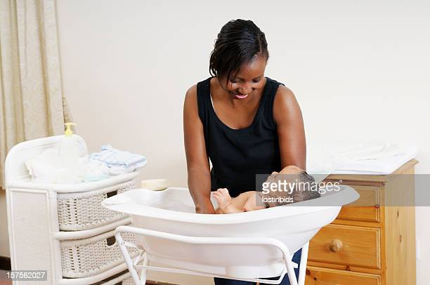 African American Woman Supporting And Washing A Baby