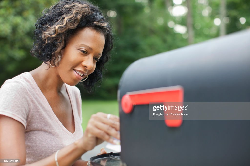 African American woman taking mail from mailbox : Stock Photo