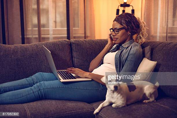 African American woman talking on mobile phone and using laptop.