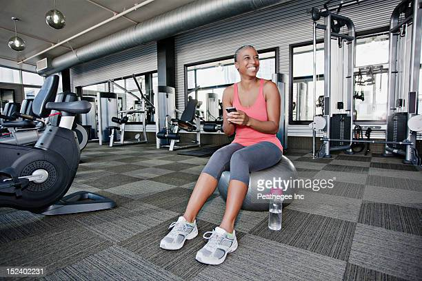 African American woman text messaging on cell phone in health club